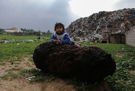 A child plays on a huge stone during a cold weather wave in the outskirts of the poor neighbourhood of Khan Yunis refugee camp.