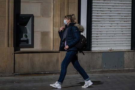A woman wearing a face mask as a precaution against the spread of Coronavirus walks through the centre of San Sebastian. Spanish Prime Minister Pedro Sánchez has declared a state of emergency in Spain because of Covid-19 outbreak, after the raise of number of cases of people infected with Covid-19 in the country. Spanish authorities have closed museums and monuments to control the expansion of Covid-19 outbreak. The Basque Country is one of the areas of Spain where there have been more infections.