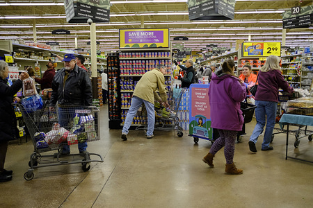 BLOOMINGTON, UNITED STATES - MARCH 18, 2020: Shoppers fill a Kroger grocery store stripping many shelves clean of merchandise, during the Covid-19 national emergency. Indiana governor Eric Holcomb banned in-person dining in all restaurants, shut down all bars, in the Indiana. Due to panic shopping, and some people hoarding, hand sanitizer, and other disinfectants are hard to find in the community, so Cardinal Spirits made the hand sanitizer to offer to the public.