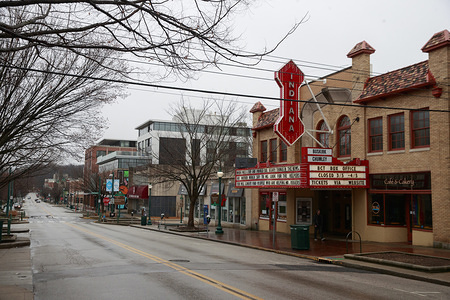 """BLOOMINGTON, UNITED STATES - MARCH 18, 2020: A quote attributed to Mr. Rogers fills the marquee above the Indiana Theater in deserted downtown where parking it normally very difficult to find during the Covid-19/Coronavirus emergency in Bloomington. When I was a boy and I would see scary things in the news, my mother would say to me, """"Look for the helpers. You will always find people who are helping,"""" Fred Rogers."""