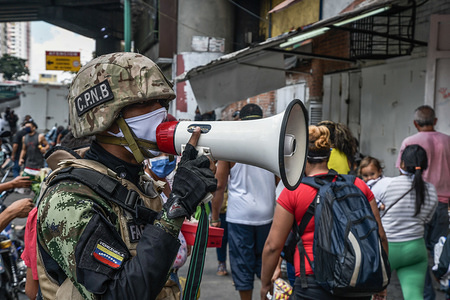 A police officer is seen using a megaphone alerting people about the coronavirus and telling them to go home. After 3 days of quarantine decreed by the government of President Nicolas Maduro, so far the figure of 36 people confirmed to be infected with COVID-19 remains. Results are expected from more than 120 samples that have been sent by the hygiene institute. Security agencies continue to close businesses and try to keep people in their homes to prevent the virus from spreading further.