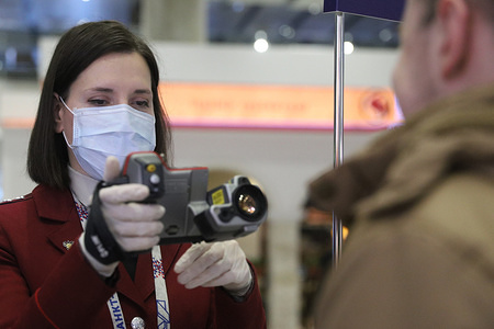 An employee of the Russian Federal Service for Surveillance on Consumer Rights Protection and Human Wellbeing (Rospotrebnadzor) checks the body temperature of a man with the infrared thermometer during the corona virus pandemic. A special outdoor screening station for COVID-19 coronavirus was opened at Pulkovo airport. At least 253 cases of coronavirus have been confirmed in Russia.