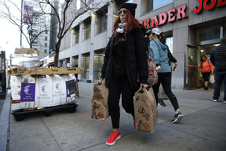 NEW YORK, UNITED STATES - MARCH 21, 2020: A shopper exits a Trader Joes supermarket after stock up on supplies. As the coronavirus (COVID-19) continues to spread throughout the United States, New Yorkers continue with daily routines   limited to shopping and other essential tasks. On March 21, 2020 Governor Andrew Cuomo of New York announced that New York City has become the epicenter of the coronavirus surpassing 10,000 cases.