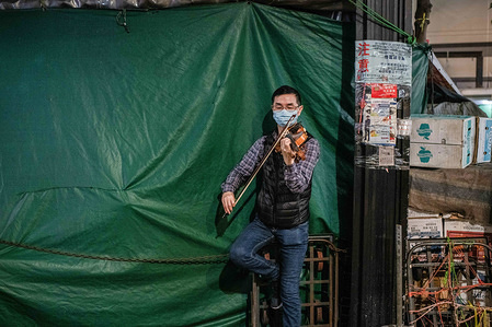 A musician wearing a face mask as a precaution against the spread of Coronavirus plays a violin on a street at the Central district in Hong Kong.As the coronavirus pandemic worsens, millions of people are struggling to adjust to their new reality. Sanitary precautions, wearing masks in public space and quarantines are some of the governmental and self-imposed measures. The World Health Organization called a global health emergency, reversing earlier decision on coronavirus outbreak.