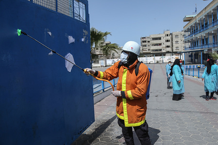 A civil worker disinfectants the doors of UNRWA school as a preventive measure against the spread of Coronavirus in Khan Yunis. Test results confirm two cases in Gaza hence recording the first cases of COVID-19 in the Hamas-controlled strip.