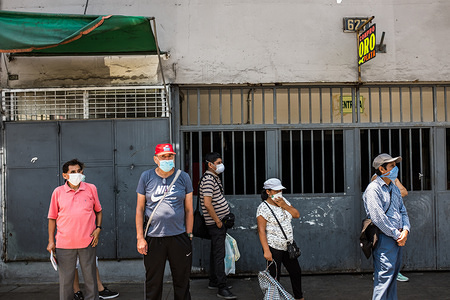 People wearing face masks as a precaution against the spread of Coronavirus wait at the bus stop. Due to the threat of the coronavirus pandemic, on March 15 President Vizcarra declared the national state of emergency and the suspension of the exercise of constitutional rights related to personal freedom and security, inviolability of the home and freedom of assembly and transit in the territory for 15 days. Currently, in Peru there are 416 registered cases and 7 deaths from Covid-19.