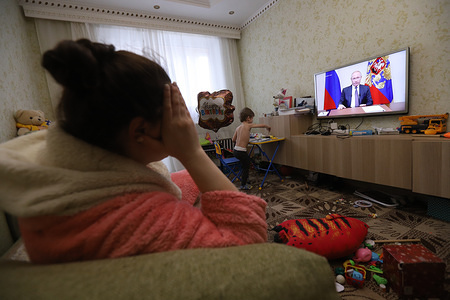 In this photo illustration a woman watching President, Vladimir Putin addressing the nation about COVID-19 situation in Russia. Referendum on constitutional amendments postponed indefinitely. At least 658 cases of coronavirus have been confirmed in Russia.