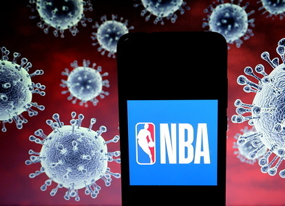 In this photo illustration a National Basketball Association (NBA) logo seen displayed on a smartphone with a computer model of the COVID-19 coronavirus in the background.