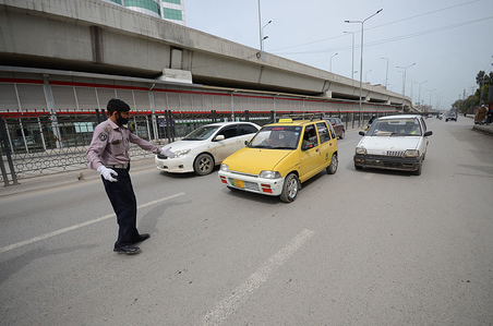 Policemen inspect vehicles during the lock down at a checkpoint amid Coronavirus fears in Peshawar.