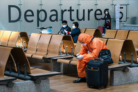 A man wearing a protective suit sits at the departure hall. Number of Incheon Airport passengers falls to record low amid coronavirus(COVID-19) spread.
