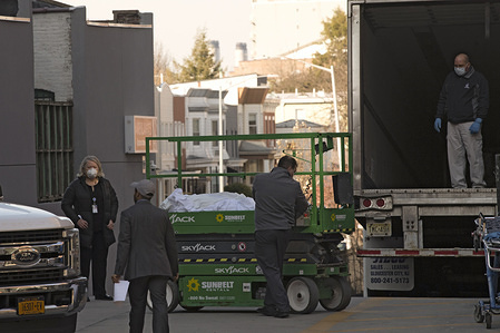 NEW YORK, UNITED STATES - MARCH 26, 2020: (EDITOR'S NOTE: Image depicts death) Workers move corpses into a refrigeration truck outside Mount Sinai Hospital in the Queens borough of New York City during the corona virus pandemic. The COVID-19 outbreak in New York City has quickly overwhelmed local hospitals with patients of the coronavirus.