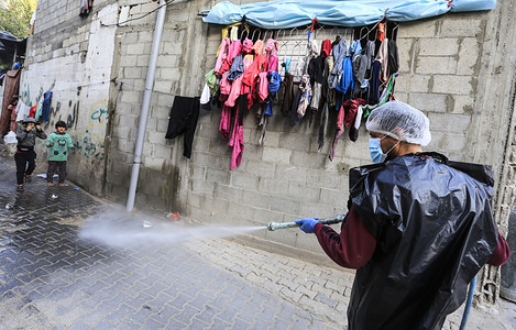 A Palestinian disinfects the streets of the Jabalia refugee camp as a precaution against the spread of coronavirus Covid-19 in the northern Gaza Strip. Palestinian Ministry of Health has confirmed 9 new Covid-19 coronavirus cases in the Gaza Strip.