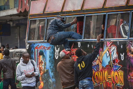A man enters a public bus through the window on day one of the curfew. A countrywide curfew was imposed by President Uhuru Kenyatta as a preventive measure against the spread of coronavirus. Kenya has so far recorded only 31 cases and 1 death of covid-19.