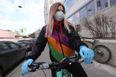 A woman wearing a face mask and gloves as a precaution against the spread of Coronavirus rides a bicycle during the first day off work week. A week from 28 March till 5 April declared off work in Russia to minimise the spread of the Coronavirus (COVID-19).