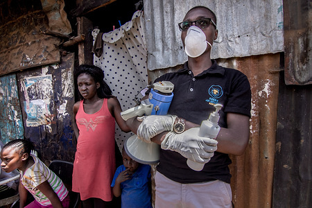 A local health worker wearing a protective mask and gloves sensitises residents on how to stay safe and be aware of Coronavirus. Kenya Coronavirus cases rise to 38 as 7 new infections are confirmed.