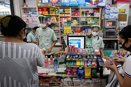 Cashiers in a 7-11 retail store wear face shields while serving their customers as a preventive measure against the spread of coronavirus. Thai Public Health Ministry reports 120 new cases of coronavirus (Covid-19), raising the total to 1,771 and 12 deaths.