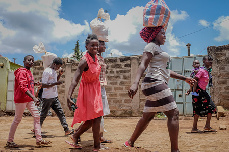 A group of young women heading home carrying bags of food Donated by local organisations during the curfew. Following the corona virus pandemic, the government of Kenya imposed a curfew which has rendered many income less and escalating the food crisis which forces many from the poor communities to move out without any protection disregarding their healthy.