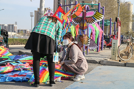 A woman wearing a protective mask sales kite at a public square in Yinchuan.