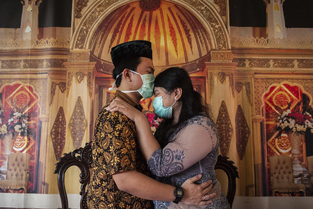 Bride and groom kiss while wearing face masks as a preventive measure, during a wedding solemnisation (ijab Kabul) at the Religious Affairs Office. Many couples in Indonesia have postponed or cancelled their wedding receptions due to the Covid-19 pandemic. Indonesia has reported 1790 people infected and 170 dead as of 2 April 2020.