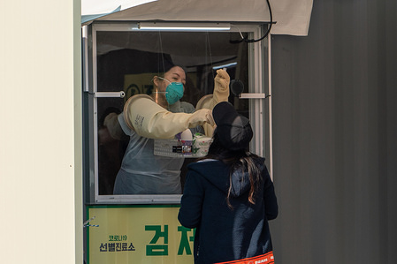 A medical staff wearing a protective suit as a preventive measure, collects samples from a resident at the 'Walk Thru' centre. The Seoul government opened a 'Walk Thru' centre testing for corona virus cases only for residents in Seoul coming from abroad in response to the global coronavirus(COVID-19) pandemic.