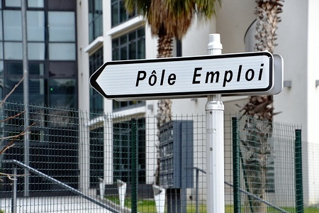 """A signpost showing the direction of a """"Pole emploi"""" agency. """"Pole emploi"""" is a public establishment responsible for employment in France."""