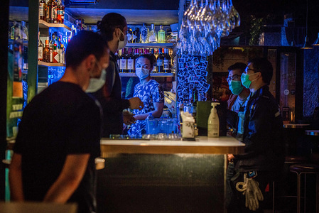Police agents speak with the manager of a pub at the Hong Kong district of Soho during the coronavirus crisis. Bars in Hong Kong, have been temporarily shut their doors as government orders two-week shutdown from 6pm on Friday, April 3rd to curb Covid-19 spread. Any place exclusively or mainly used for sale or supply of alcohol are oblige to close its doors.