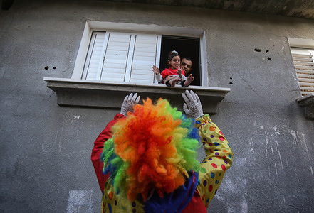 A palestinian youth dressed as a clown while wearing a protective gloves and a mask, staged a street performance to entertain children trapped at home due to the Corona Virus outbreak in Khan Yunis, southern Gaza Strip.