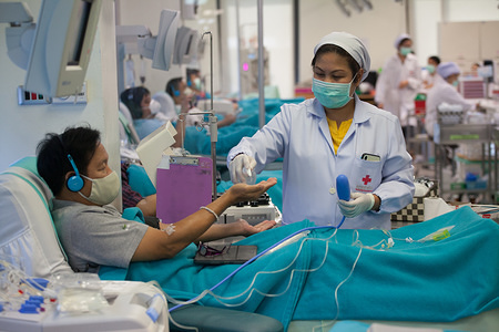 A nurse wears a protective mask sprays alcohol on a donor from donating room. Thai Red Cross has requested to donate plasma blood from patient recovered from COVID-19 .
