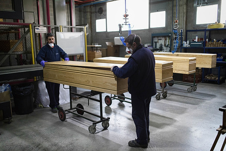 Two workers seen working at a coffin factory. The Eurocoffin coffin factory, the largest in Catalonia has tripled its production since the beginning of the corona virus pandemic, going from manufacturing 60 coffins to 160 coffins per day. Despite having a wide catalog of coffins, these days only three models are being manufactured, the cheapest and fastest to manufacture.
