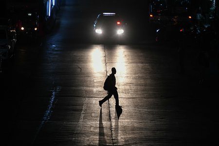 A man crosses the street at Khlong Toei market area, Bangkok.