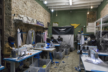 Members of the Sindicato de Manteros make gowns for medical staff. In the heart of the Raval district, street vendors of Barcelona, known as Sindicato de Manteros, turn their clothing store into a workshop of masks and medical gowns for health care staff to fight against the Coronavirus (Covid-19) pandemic. The Sindicato de Manteros was born in 2015, when street vendors in Barcelona organised themselves to defend their rights.