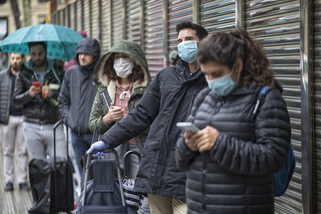 """People wearing face masks as preventive measure wait in a queue to enter a supermarket.  The population is asked  to keep a """"social distance"""" between 1.5 meters and 2 meters to avoid the spread of coronavirus. Due to the confinement order in Spain decreed by the Spanish President Pedro Sanchez to fight against the Coronavirus (Covid-19) the cities are practically empty."""