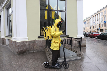 A courier of Russian delivery service Yandex Eda in a protective mask rides past Macdonalds restaurant. All days until 30 April were declared off work days by President Vladimir Putin. Russia has 6 343 confirmed cases of COVID-19.
