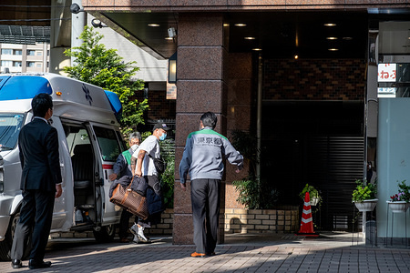 TOKYO, JAPAN - APRIL 7, 2020: A COVID-19 coronavirus patient leaves the ambulance as he arrives at the Tokyo In Hotel which is currently used to accommodate COVID-19 coronavirus patients with mild symptoms. The Tokyo Inn hotel is being used to accommodate COVID-19 coronavirus patients who has mild symptoms in order to free up hospital beds for those who need intensive care.