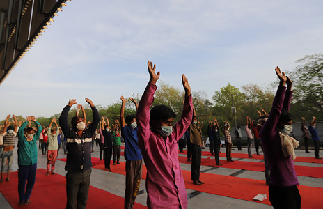 DELHI, INDIA - APRIL 7, 2020: Daily wage workers and homeless people perform yoga at Yamuna Sports complex which was converted into a makeshift camp for those stranded in Delhi without a home during a nationwide lockdown in the wake of coronavirus pandemic. Indian Government imposed a 21-day nationwide lockdown to minimise the spread of Coronavirus (Covid-19) disease.