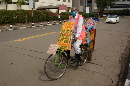 A man raising awareness about corona virus rides his bicycle wearing a face mask as a preventive measure in Nairobi during the pandemic.  Kenya on April 7, 2020 confirmed 14 more cases of Coronavirus, bringing the total number of those affected to 172.