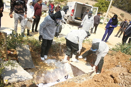Health workers wearing protective suits as a preventive measure, burying the corpse during the white operation. A grand burial named 'white operation' for corona virus victims. Tunisia has recorded a total of 650 infected cases and 23 deaths by the covid-19 disease.