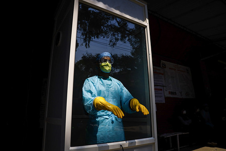 A medical person stands inside a corona virus check-up booth wearing proper protective gear at Bhaktapur Hospital, during the fifteenth day of a nationwide lockdown.Nepal government extended its nationwide lockdown till April 15 in an effort to combat the spread of coronavirus/COVID-19.