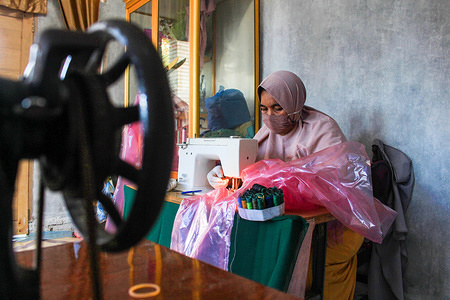A tailor making home-made protective gear during the corona virus pandemic. Face masks and Personal Protective Equipment (PPE) have become hard to obtain due to the coronavirus pandemic restrictions and other related factors thus resorting to home-made equipment from fabric.