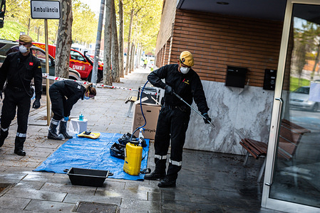 """Military officers wearing face masks as a preventive measure, spraying the entrance during the disinfection. The military (UME) disinfect the """"Residencia de Gent Gran"""" a nursing home where at least 5 people died of the Covid-19. Spain Health Ministry has so far recorded a total of 146,690 infections, 14,673 death and 48,021 recovered since the beginning of the corona virus outbreak."""