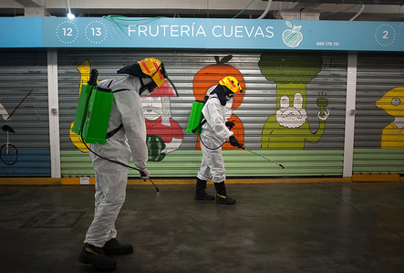 Firefighters wearing protective gear as a preventive measure, spray outside stores during the disinfection. Firefighter disinfect the municipal market following the confinement decreed by the Spanish government and will be extended for more 15 days until 26 April.