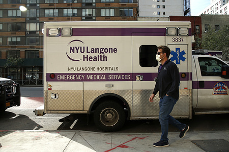 NEW YORK, UNITED STATES - APRIL 8, 2020: A man passes by an ambulance parked by NYU Langone Hospital. With the mounting cases of COVID-19, the call centers around the city have seen a 50 percent rise in 911 calls overwhelming the Emergency Services Technicians personnel. Consequently, FEMA has sent 250 ambulances and 500 EMT personnel to New York. Additionally, while there are no exact numbers of personal protective equipment (PPE) FEMA has sent to hospitals, shortages continue.