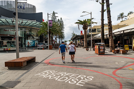 GOLD COAST, AUSTRALIA - APRIL 09, 2020: A couple walk on a deserted Cavill Avenue Street in Surfers Paradise. Council has taken an extraordinary step of closing some Gold Coast beaches as a preventive measure against the spread of Coronavirus after thousands of people ignored social distancing rules. Beaches at The Spit, Surfers Paradise and Coolangatta will shut from midnight. The remainder of the city's beaches will stay open for people to exercise, swim or surf, but Council says it won't hesitate to close more beaches if people continue to flout the rules.
