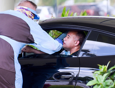 MELBOURNE, FLORIDA, UNITED STATES - APRIL 8, 2020: A man in a car gets tested for the coronavirus with a nasal swab on the second day of a drive-thru COVID-19 test collection facility operated by Omni Healthcare. The facility is prepared to test at least 500 people per day, seven days a week, by appointment.