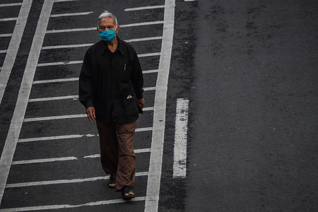 A man walks along the road while wearing a protective mask as a preventive measure against the spread of Coronavirus. Indonesian ministry of health confirmed 3,293 cases of COVID-19, 252 people recovering and 280 deaths.