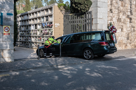 A hearse entering the Girona cemetery during the funeral procession amid coronavirus outbreak. The Covid-19 makes funerals difficult, the situation requires cemeteries to be kept closed as a precautionary measure and only open when there is a burial funeral taking place. Relatives of the deceased aren't allowed to attend the ceremony thus the law allowing a maximum of 3 to 5 people.