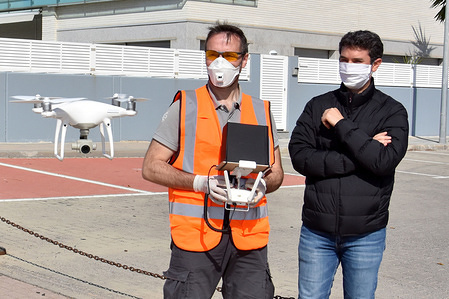 A drone pilot operator from a company TECH DRONE shows the mayor Kenneth Martinez how a drone monitors the streets of El Vendrell during the home confinement in a bid to slow down the spread of COVID-19 pandemic. The Local Police uses a drone controlled by an operator from a company TECH DRONE to monitor the streets of El Vendrell so that people do not violate the confinement decreed by the Government of Spain for the health crisis of the Covid-19 coronavirus.