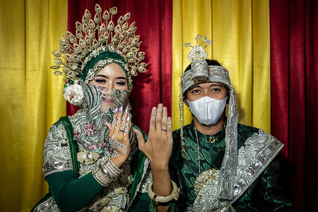 SIWA, INDONESIA - APRIL 9, 2020: Groom Evo Darmawangsah (R) and bride Silviana Dewi (L) show off their rings during their wedding ceremony amid COVID-19 outbreak in Siwa. The pandemic has spread to all provinces in Indonesia except Gorontalo. All had reported suspected cases. So far, Indonesia has recorded 280 deaths, more than any other Southeast Asian country.