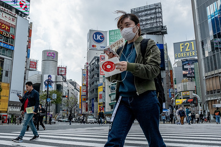 TOKYO, JAPAN - APRIL 9, 2020: Less people in Shibuya than usual, people are wearing face mask for protection. The Japan government declared a state of emergency to cover Tokyo, Osaka, also covers Saitama, Kanagawa, Chiba, Hyogo and Fukuoka prefectures on the 7th April and will continue until at least May 6. Tokyo governor Yuriko Koike has asked residents to self-isolate as COVID-19 coronavirus spreads.
