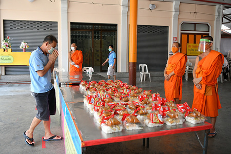 A man greets a monk before receiving a free meal at the Wat Arun Buddhist temple in Bangkok. The Wat Arun temple is providing two free meals a day for people in need whose livelihood has been affected due to the emergency regulations enforced in Thailand to control the spread of coronavirus.